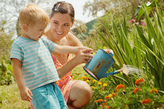 Woman with a little son watering flowers. Little boy with his mother watering from a watering can. Summer, sunny day Royalty Free Stock Photos