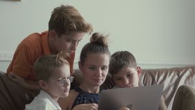 Woman with little sons watches movie on laptop at home stock video
