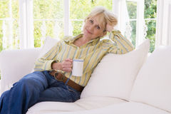 Woman in living room with coffee smiling Stock Image