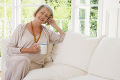 Woman in living room with coffee smiling Royalty Free Stock Photo