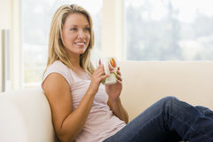 Woman in living room with coffee smiling Royalty Free Stock Photography