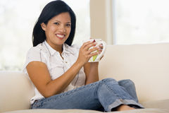 Woman in living room with coffee smiling Royalty Free Stock Images