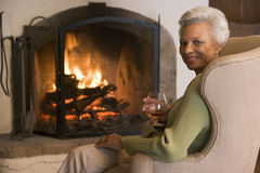 Woman in living room with drink smiling Stock Photography
