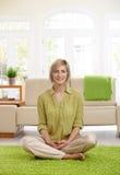 Woman on living room floor Stock Photos