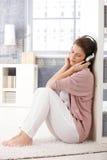 Woman on living room floor with headphone Stock Photo