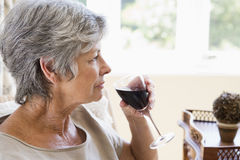 Woman in living room with glass of wine Stock Image