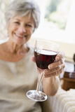 Woman in living room with glass of wine smiling Royalty Free Stock Photo