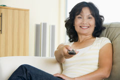 Woman in living room holding remote control Stock Photo