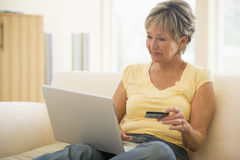 Woman in living room laptop and credit card Royalty Free Stock Photos