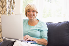 Woman in living room with laptop smiling Stock Image