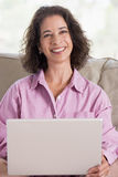 Woman in living room with laptop smiling Stock Images