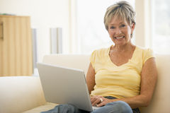 Woman in living room with laptop smiling Royalty Free Stock Photo
