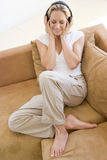 Woman in living room listening to headphones Stock Photo