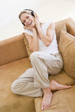 Woman in living room listening to headphones Stock Images