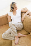 Woman in living room listening to headphones Stock Photography
