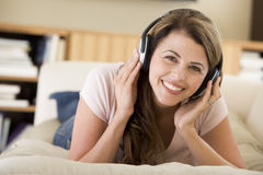 Woman in living room listening to headphones. Smiling royalty free stock images