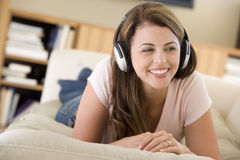 Woman in living room listening to headphones. Smiling stock photos