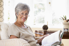 Woman in living room reading book smiling Royalty Free Stock Photos
