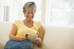 Woman in living room reading book smiling Royalty Free Stock Image