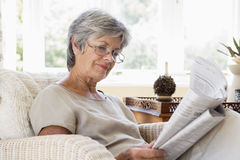 Woman in living room reading newspaper Stock Photography