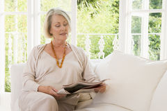 Woman in living room reading newspaper Stock Photos