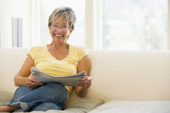 Woman in living room reading newspaper smiling Royalty Free Stock Photos