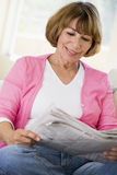 Woman in living room reading newspaper smiling Royalty Free Stock Photo