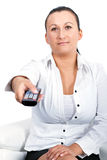 Woman in living room with remote control Stock Photo
