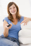 Woman in living room with remote control Stock Photography