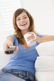 Woman in living room with remote control Royalty Free Stock Photo