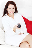Woman in living room with remote control in hand Stock Photo