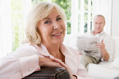 Woman in living room smiling and man with paper Stock Photography
