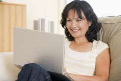 Woman in living room using laptop stock images