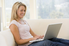 Woman in living room using laptop smiling Stock Photo