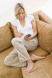 Woman in living room using PDA Stock Image