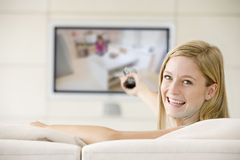 Woman in living room watching television Stock Images