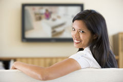 Woman in living room watching television Royalty Free Stock Image