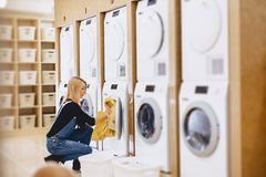 A woman load the sheets in the laundry to wash and dry stock photography