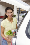 Woman loading car with grocery bags in supermarket car park, smiling, portrait Royalty Free Stock Photography