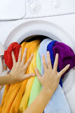 Woman loading clothes in the washing machine Stock Photos