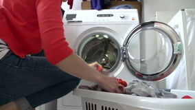 Woman Loading Clothes Into Washing Machine Stock Photos
