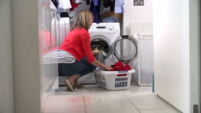 Woman Loading Clothes Into Washing Machine Royalty Free Stock Image
