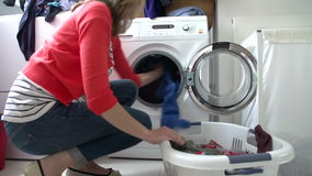 Woman Loading Clothes Into Washing Machine stock video footage
