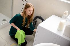 Woman loading clothes into washing machine. Young blond woman loading clothes into washing machine in bathroom Stock Image