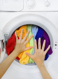 Woman loading colorful laundry in the washing machine Stock Image