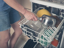 Woman loading dish washer Royalty Free Stock Photo