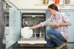Woman Loading Dishwasher In Kitchen. Woman In Kitchen Loading Dishwasher Stock Photos