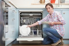 Portrait Of Woman Loading Dishwashwasher In Kitchen Royalty Free Stock Photography