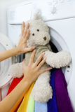 Woman loading fluffy toy in the washing machine Royalty Free Stock Photos