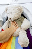 Woman loading fluffy toy in the washing machine Stock Photography